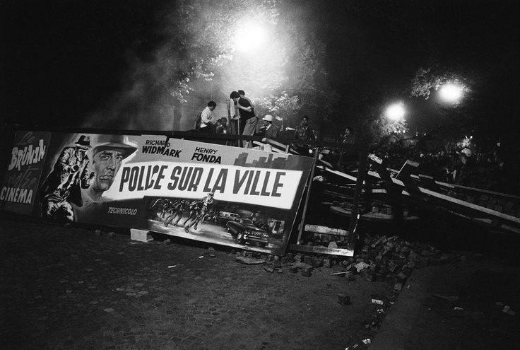 """Barricade tenue par des étudiants en Mai 68 à Paris, avec affiche du film """"Police sur la ville""""."""