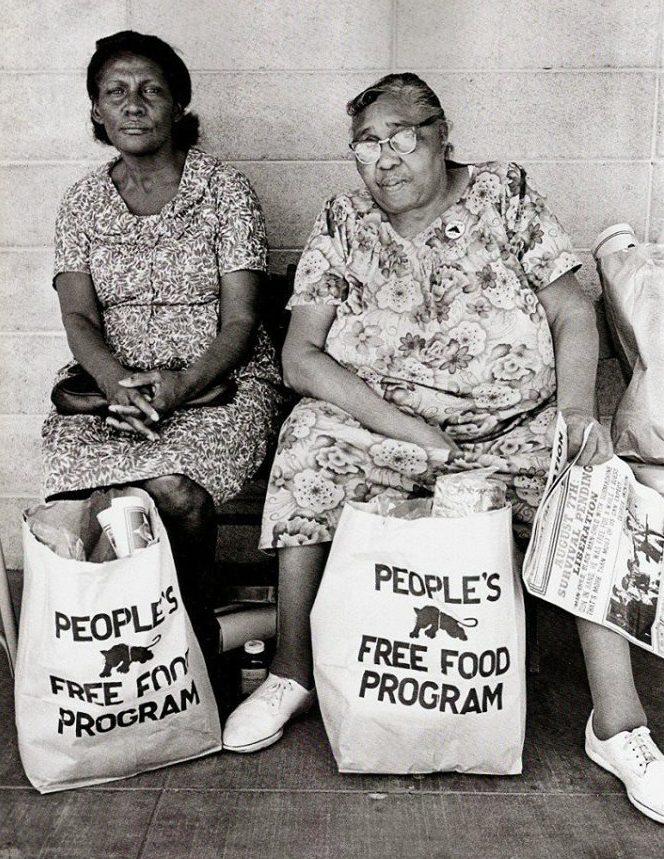 """Deux femmes portant des sacs """"People's free food program"""" - du nom de la campagne politique lancée par le BPP."""