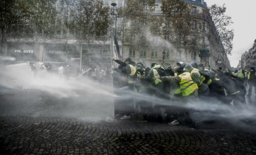 Gilets Jaunes résistant à un canon à eau sur les Champs